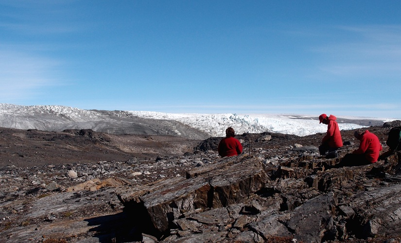 In this photo provided by Laure Gauthiez, taken in July 2012, a field team examines rocks in Greenland. Scientists have found what they think is the oldest fossil on Earth, a remnant of life from 3.7 billion years ago when Earth's skies were orange and its oceans green. In a newly melted part of Greenland, Australian scientists found the leftover structure from a community of microbes that lived on an ancient seafloor, according to a study in the Wednesday, Aug. 31, 2016, issue of the journal Nature. (Laure Gauthiez/The Australian National University via AP)
