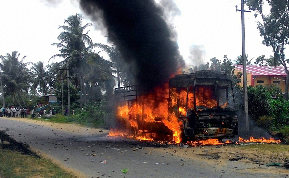 A vehicle torched by pro-Kannada activists in during a protest in Mandya district – epicentre of Mandya protest – on Monday. In view of the deteriorating situation, the Centre rushed 10 companies (about 1,000 personnel) of the special anti-riot paramilitary force RAF to Karnataka. (Photo: PTI)