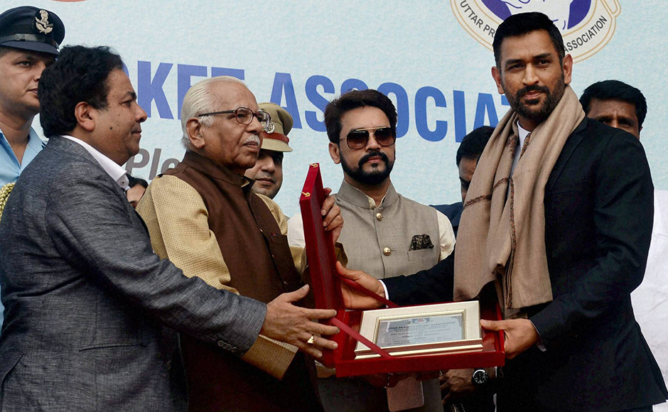 UP Governor Ram Naik and IPL Chairman Rajeev Shukla present a memento to former Indian Test captain Mahendra Singh Dhoni, as BCCI President Anurag Thakur looks on, on the occasion of India's 500th Tests match at Green Park in Kanpur on Thursday. PTI Photo(PTI9_22_2016_000041B)