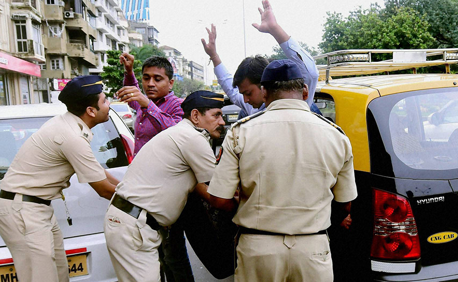 Mumbai police check passengers of a taxi at a checkpost as a high alert was issued by the Naval Quarters after two school children spotted suspicious looking gunmen at Uran, near Mumbai on Thursday. PTI Photo by Santosh Hirlekar (PTI9_22_2016_000232B)