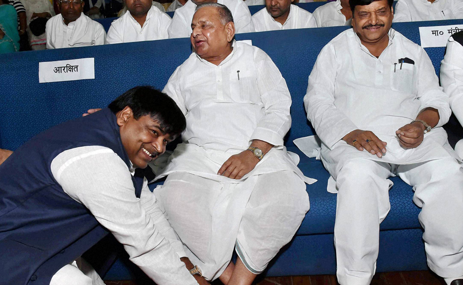 Much to the amusement of those present at the Raj Bhawan, a beaming Prajapati sat at the feet of SP supremo Mulayam Singh Yadav for photo journalists. (Photo: PTI)