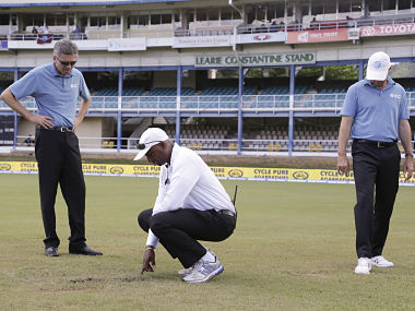 Umpires Nigel Llong, left, Gregory Brathwaite, center, and Rod Tucker inspect the field as a wet ground delays the start of day three of the fourth cricket Test match between India and West Indies at Queen's Park Oval. AP