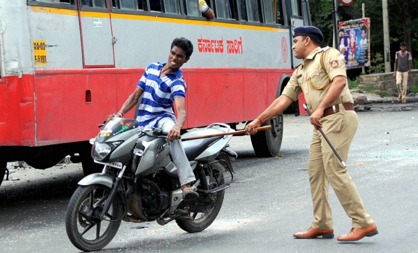 A policeman charges a miscreant riding a motorcycle during prohibitory order at Sunkadakatte in Bengaluru on Tuesday. PTI