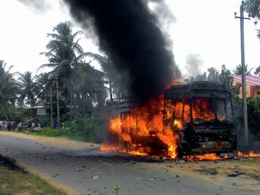 A vehicle in flames after being torched by pro-Kannada activists. PTI