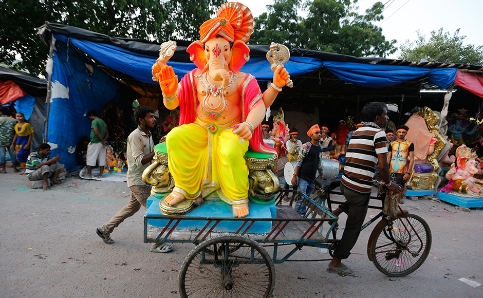 Indians transport an idol of elephant headed Hindu god Ganesha on a cycle rickshaw on the eve of Ganesh Chaturthi festival in Ahmadabad, India, Sunday, Sept. 4, 2016. The idol will be immersed in water bodies after worship at the end of the festival. (AP Photo/Ajit Solanki)