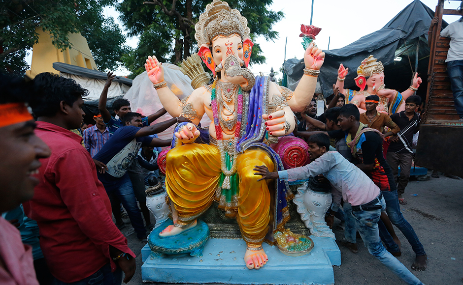 Indians prepare to load an idol of elephant headed Hindu god Ganesha on to a vehicle on the eve of Ganesh Chaturthi festival in Ahmadabad, India, Sunday, Sept. 4, 2016. The idol will be immersed in water bodies after worship at the end of the festival. (AP Photo/Ajit Solanki)