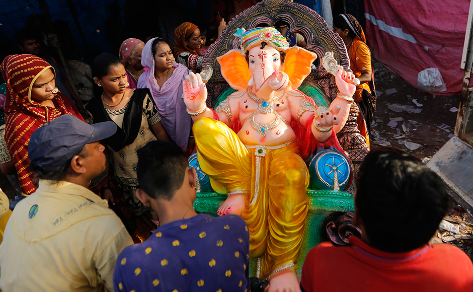 Indians carry an idol of elephant headed Hindu god Ganesha on the eve of Ganesh Chaturthi festival in Ahmadabad, India, Sunday, Sept. 4, 2016. The idol will be immersed in water bodies after worship at the end of the festival. (AP Photo/Ajit Solanki)
