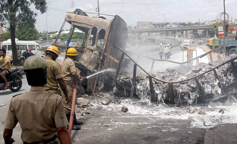Fire men dousing a torched truck in Bengaluru on Tuesday. Additional forces have been deployed in the city to curb further loss of property. PTI