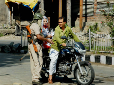 Security guard checks the curfew of a couple in Srinagar. PTI