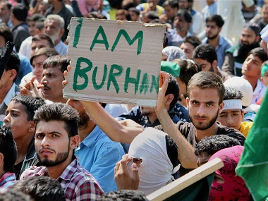 A youth displays a placard during a protest rally against the visit of the all-party delegation and civilian killings, at Palpora in Srinagar on Monday. PTI