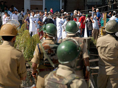 Security personnel watch as masked youth shouts slogans after they took out a protest rally against the killings of civilians, in Srinagar. PTI