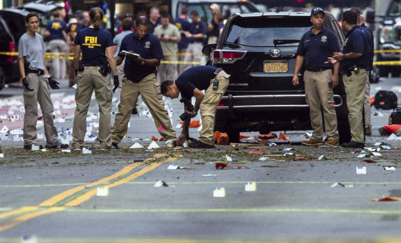 FBI officials search the site of attack. AP