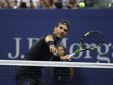 Rafael Nadal celebrates by hitting a ball into the stands. Reuters