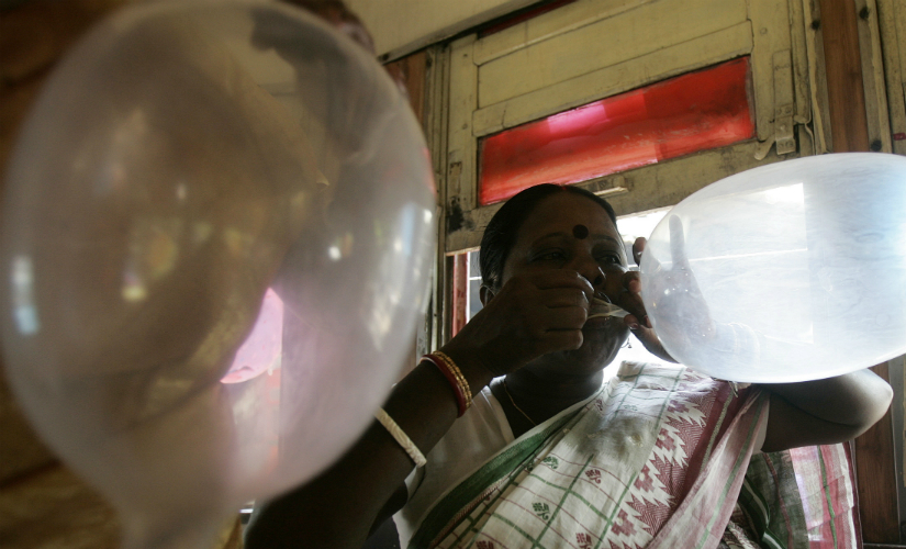 A file image of a sex worker blowing a condom during an AIDS awareness campaign in Kolkata. Reuters