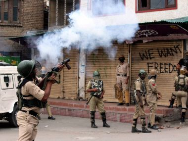 Security jawans fire tear gas shells to disperse protesters who staged a protest march towards Lal Chowk in Srinagar on Thursday. PTI