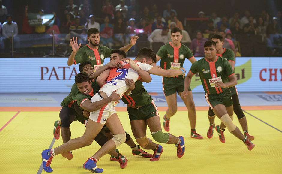 England kabaddi player, Keshav Gupta (C) struggles to free himself from Bangladeshi opponents during a match between England and Bangladesh at the TransStadia in Ahmedabad on October 8, 2016. The 2016 Kabaddi World Cup tournament runs from October 7 - 22, 2016.