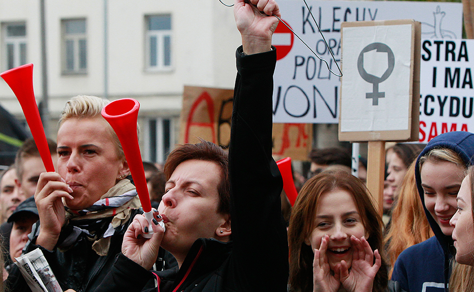 """Polish women and some male supporters blow horns while raising a hanger, the symbol of illegal abortion, during a nationwide strike and demonstration to protest a legislative proposal for a total ban on abortion in Warsaw, Poland, Monday, Oct. 3, 2016. Polish women are waging a nationwide strike to protest a legislative proposal for a total ban on abortion, with workers and students boycotting their jobs and classes and housewives refusing to do housework. Some businesses and restaurants are also closed on what is being called """"Black Monday,"""" an expression of outrage against a proposal to further restrict an abortion law that is already one of the most limited in Europe. AP"""