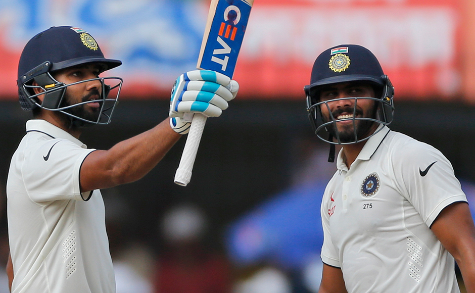 Indian batsman Rohit Sharma, left, celebrates his half century with Ravindra Jadeja during the second day of the third test cricket match between India and New Zealand in Indore, India on Sunday