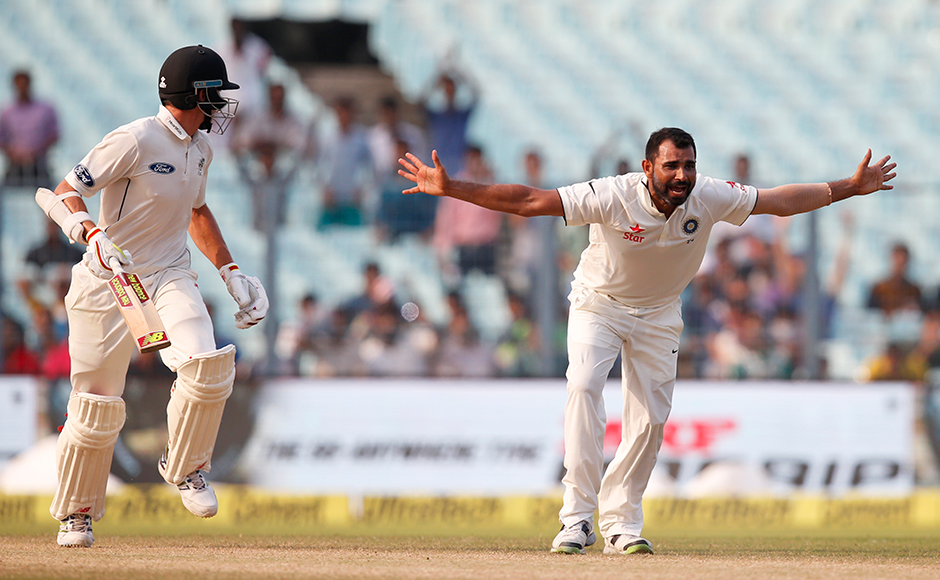 Indian bowler Mohammed Shami successfully appeals for the wicket of New Zealand's Mitchell Santner, left, on the fourth day of the second cricket test match in Kolkata, India, Monday, Oct. 3, 2016. AP