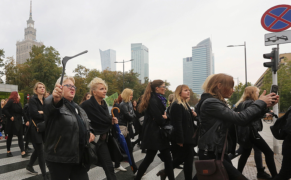 """A large crowd gathered in the rain in central Warsaw and people were out on the streets in other cities. People held up signs, including """"My body, My choice,"""" as well as coat hangers — a symbol of dangerous illegal abortions protesters fear could become more common. The day of action also included a call for housewives to refuse to do housework. (Photo: AP)"""
