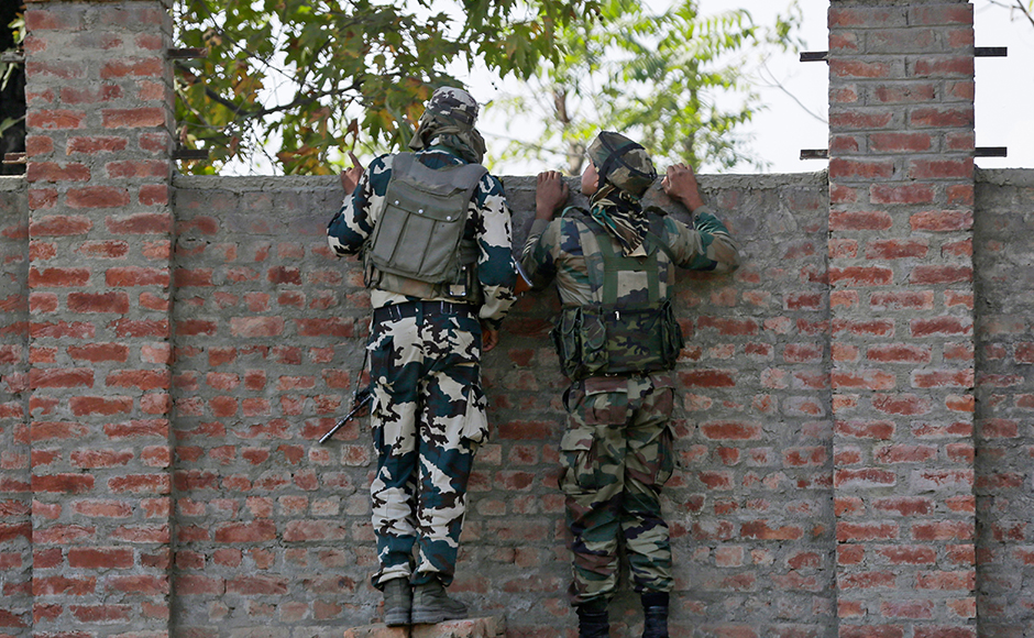Indian soldiers keep a watch at a government building where suspected militants have taken refuge during a gun-battle in Pampore, on the outskirts of Srinagar, Indian controlled Kashmir, Monday, Oct. 10, 2016. Government forces were battling a group of suspected rebels inside a government compound on Monday in the Indian-controlled portion of Kashmir. AP