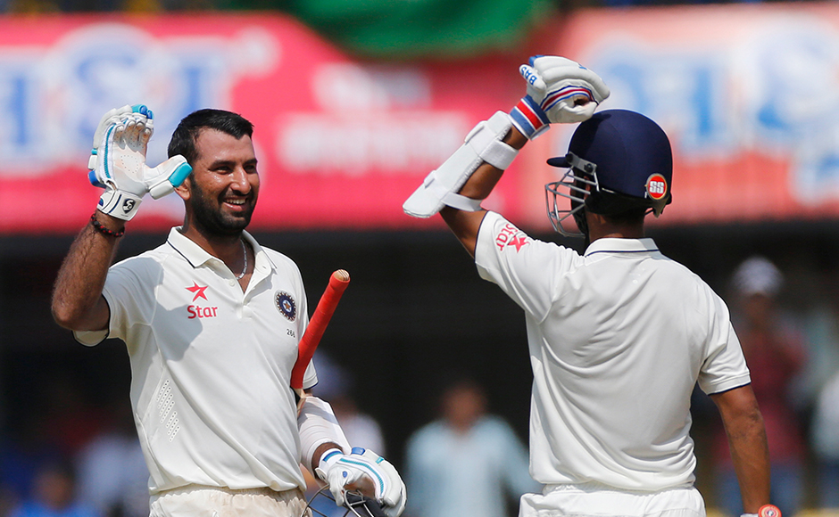 Indian batsman Cheteshwar Pujara, left, celebrates his century with Ajinkya Rahane during the fourth day of the third test cricket match between India and New Zealand in Indore, India, Tuesday, Oct. 11, 2016. (AP Photo/Rafiq Maqbool)