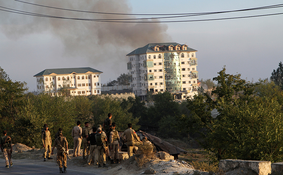 Jammu and Kashmir policemen watch from a distance as smoke rises from a government building where suspected militants have taken refuge during a gun battle in Pampore, on the outskirts of Srinagar, Indian controlled Kashmir, Monday, Oct. 10, 2016. On Monday, government forces were battling a group of suspected rebels near a highway running by saffron-rich Pampore town, on the outskirts of the region's main city of Srinagar. AP