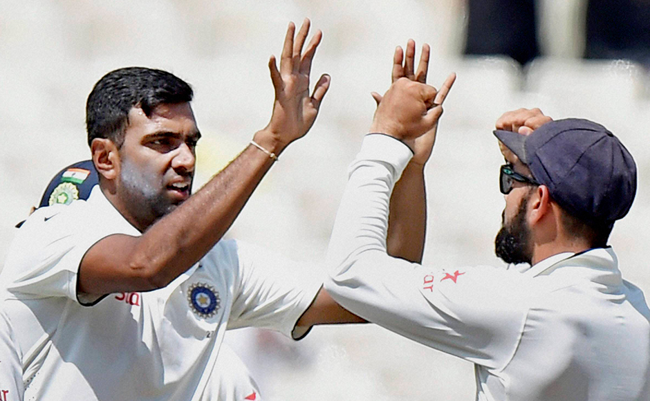 Indian bowler R Ashwin with skipper Virat Kohli celebrates a wicket during the 4th day of 2nd Test Match against New Zealand at Eden Garden in Kolkata on Monday. PTI Photo by Ashok Bhaumik (PTI10_3_2016_000064B)