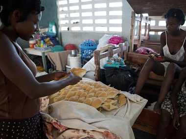 A woman whose home was destroyed by Hurricane Matthew prepares bread with peanut butter for a customer who, along with her, sought shelter inside a school in Port Salut, Haiti, Tuesday, Oct. 11, 2016. Dina Joseph, 29, not pictured, started the small business inside the classroom where her family sleeps, selling bread, dried fish, green onions and bullion cubes. The scores of people sheltering at this school have been told they have one more week before they have to move out so classes can restart. (AP Photo/Rebecca Blackwell)