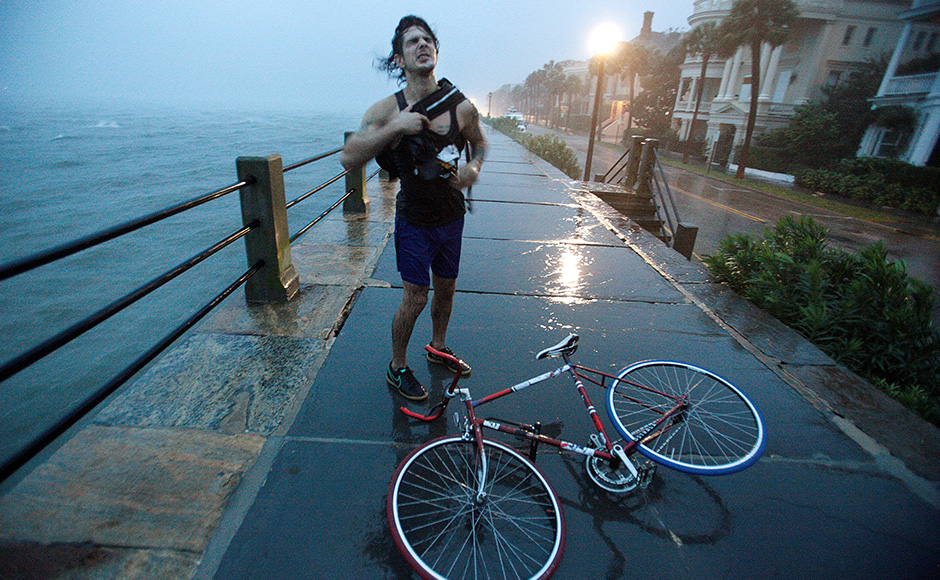 A Charleston resident reacts to the wind and rain as he pauses with his bicycle along the East Battery promenade on the southern tip of the city as Hurricane Matthew arrives in Charleston, South Carolina. Matthew triggered mass evacuations along the U.S. Atlantic coast from Florida northward through Georgia and into South Carolina and North Carolina. Reuters
