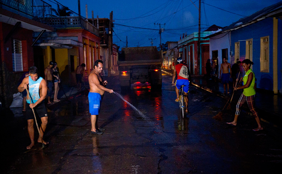 Residents clean a street muddied by the heavy rains brought by Hurricane Matthew in Baracoa, Cuba, Friday, Oct. 7, 2016. Matthew hit Cuba's lightly populated eastern tip Tuesday night, damaging hundreds of homes in the easternmost city of Baracoa but there were no reports of deaths. Water and electricity were restored to much of the town Friday. (AP Photo/Ramon Espinosa)