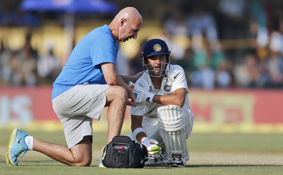 A team physiotherapist attends to Indian batsman Gautam Gambhir after the latter got injured during the third day of the third test cricket match between India and New Zealand in Indore, India, Monday, Oct. 10, 2016. (AP Photo/Rafiq Maqbool)
