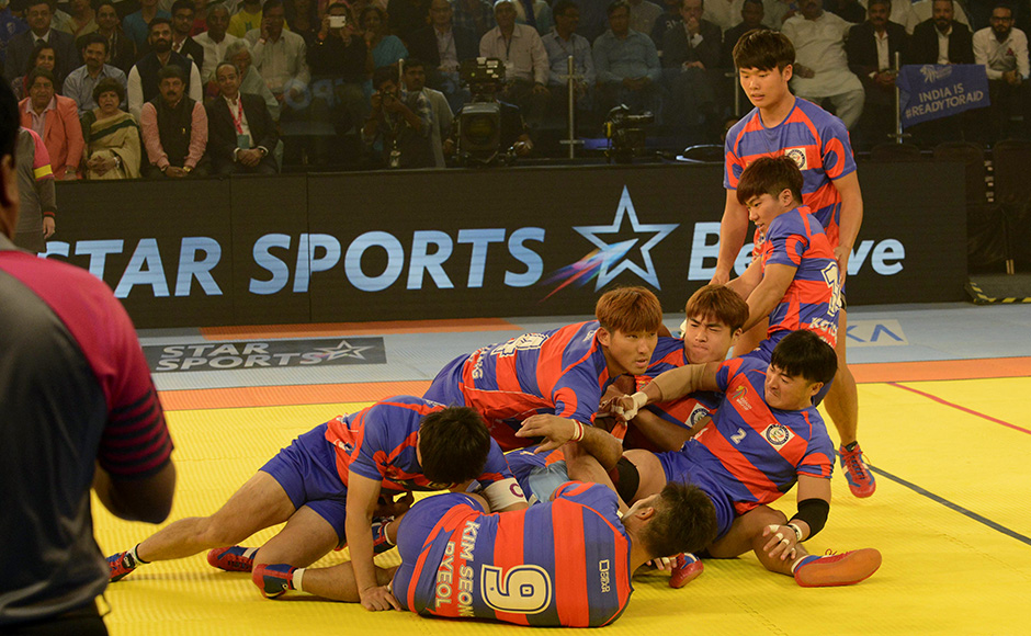 South Korean kabaddi players pounce on an Indian opponent during the 2016 Kabaddi World Cup in Ahmedabad on October 7, 2016. 12 teams from across the globe are participating in the World Cup from October 7-22. / AFP PHOTO / SAM PANTHAKY