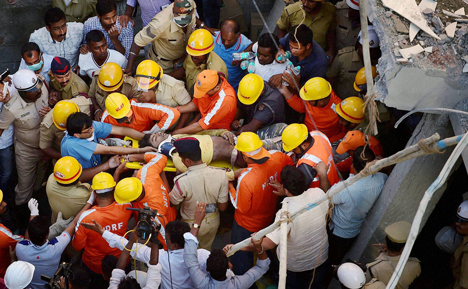 NDRF personnel carry an injured person to an ambulance after he was rescued from the rubbles of an under-construction building that collapsed in Bengaluru on Wednesday. PTI Photo by Shailendra Bhojak(PTI10_5_2016_000198B)