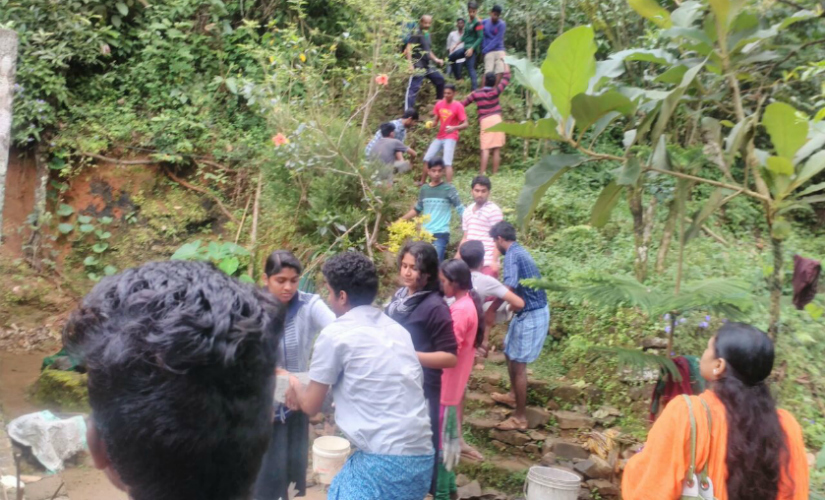 Social activists lending a helping hand to build toilet in a hilly area in Kerala. Firstpost/TK Devasia