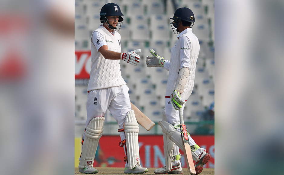 England's Joe Root, left, is congratulated by team mate Haseeb Hameed after scoring a half-century on the fourth day of their third cricket test match against India in Mohali, India, Tuesday, Nov. 29, 2016. (AP Photo/Altaf Qadri)