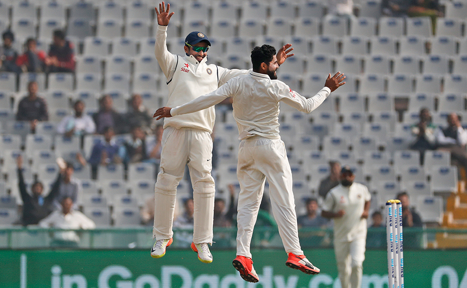 India's Ravindra Jadeja, right, and Karun Nair jump in air as they celebrate the dismissal of England's Joe Root on the fourth day of their third cricket test match in Mohali, India, Tuesday, Nov. 29, 2016. (AP Photo/Altaf Qadri)