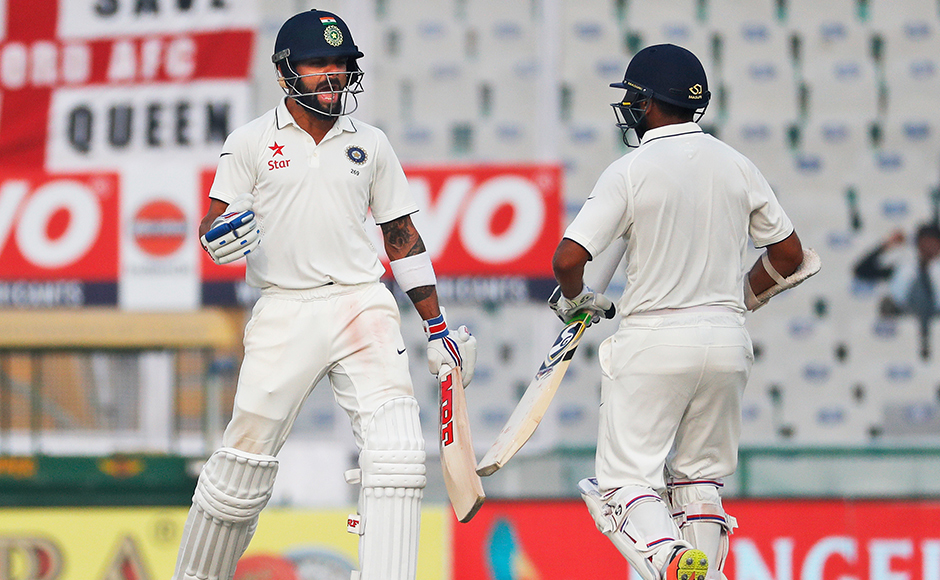 Indian test cricket team captain, Virat Kohli, left, and Parthiv Patel celebrate as India beat England on the fourth day of their third cricket test match in Mohali, India, Tuesday, Nov. 29, 2016. (AP Photo/Altaf Qadri)