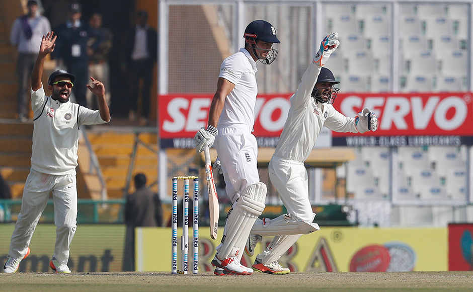 Indian wicketkeeper Parthiv Patel, right, celebrates the dismissal of England's captain Alastair Cook, center, on the first day of their third cricket test match in Mohali, India, Saturday, Nov. 26, 2016. (AP Photo/Altaf Qadri)