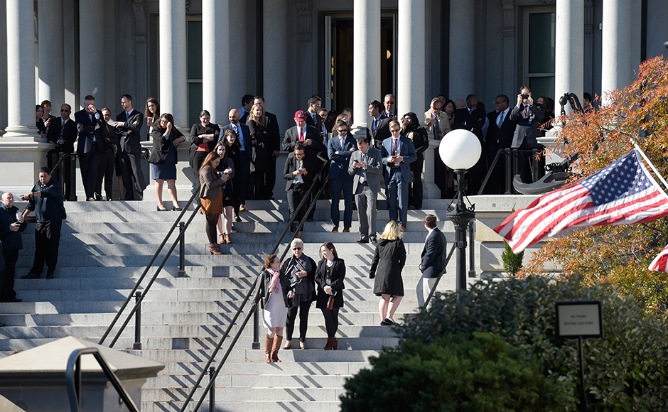 People stand on the steps of the Eisenhower Executive Office Building, next to the White House in Washington, Thursday, Nov. 10, 2016, as they wait for the arrival of President-elect Donald Trump for his meeting with President Barack Obama. (AP Photo/Susan Walsh)