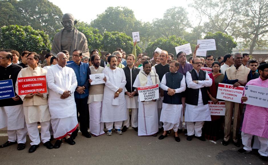 "With a united opposition protesting and almost 200 MPs from various parties participating in the discussion, the Prime Minister should explain in Parliament why he took such a decision and why he ""leaked"" the decision to his industrialist friends and BJP leaders, he said. Placard in Hindi on right reads, ""Farmers and labourers are crying, the prime minister is sleeping"". (Photo: AP)"