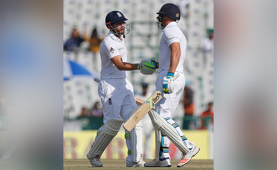 England's Jonathan Bairstow, left, is greeted by his teammate Jos Buttler after he scored half century on the first day of their third cricket test match against India in Mohali, India, Saturday, Nov. 26, 2016. (AP Photo/Altaf Qadri)