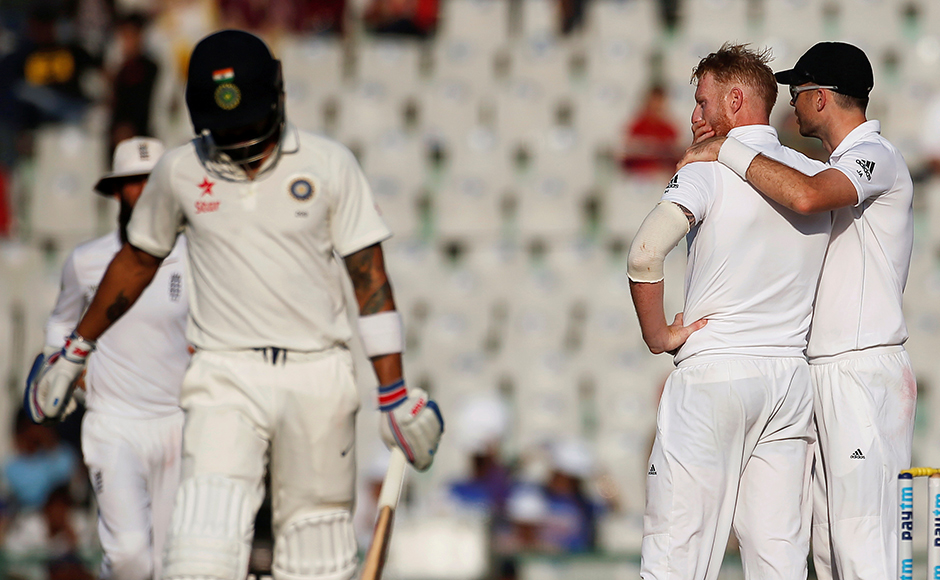Cricket - India v England - Third Test cricket match - Punjab Cricket Association Stadium, Mohali, India - 27/11/16. England's Ben Stokes (C) and James Anderson (R) celebrate the dismissal of India's Virat Kohli. REUTERS/Adnan Abidi