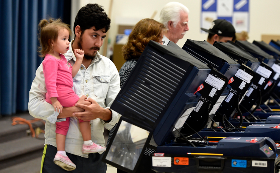 A man holds a young girl as he casts his ballot during voting in the 2016 presidential election at Robert E. Lake Elementary School in Las Vegas, Nevada, U.S November 8, 2016. REUTERS/David Becker