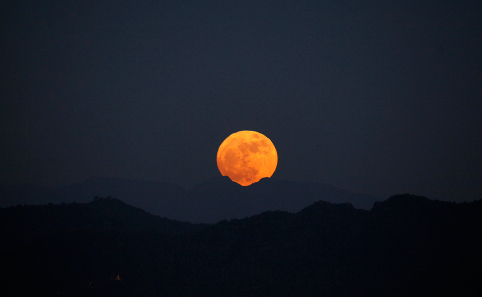 The moon rises behind the mountain range seen from Naypyitaw, Myanmar, Monday, Nov. 14, 2016. The brightest moon in almost 69 years lights up the sky in a treat for star watchers around the globe. The phenomenon is known as the supermoon. (AP Photo/Aung Shine Oo)