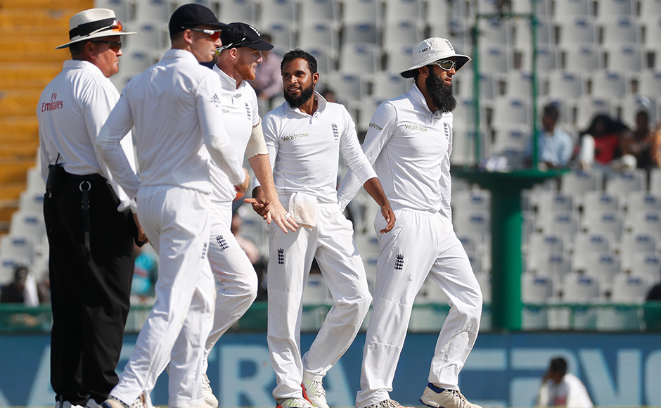 England's cricketers congratulate their teammate Adil Rashid, second from right, after taking the wicket of India's Ravindra Jadeja on the third day of their third cricket test match in Mohali, India, Monday, Nov. 28, 2016. (AP Photo/Altaf Qadri)