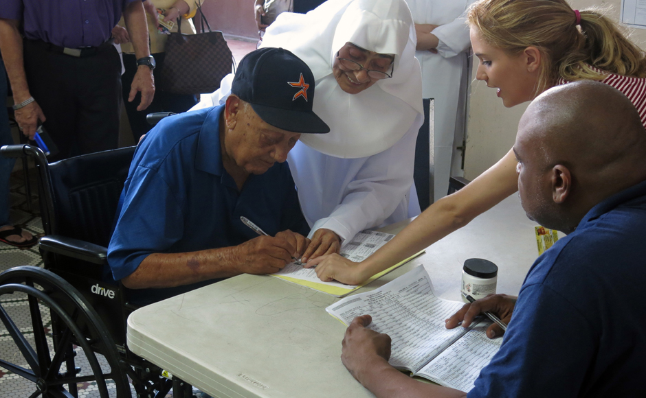 A voter signs in at a polling station to vote in the general election, at an elementary school in San Juan, Puerto Rico, Tuesday, Nov. 8, 2016. Residents of Puerto Rico are U.S. citizens, but they can't vote in the U.S. presidential election, a fact that the leading candidate for governor wants to change. (AP Photo/Danica Coto)