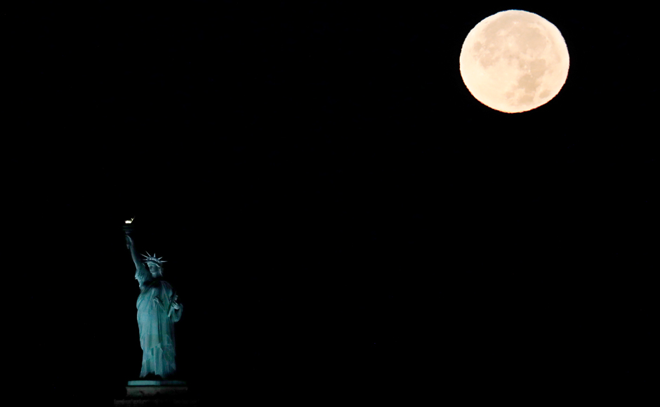 The supermoon sets behind the Statue of Liberty, Monday, Nov. 14, 2016, in New York. Monday's supermoon, a phenomenon that happens when the moon makes a close pass at the earth, is the closest to earth since 1948. (AP Photo/Julio Cortez)