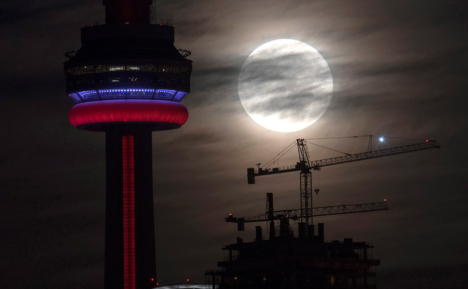 The supermoon sets behind the CN tower in Toronto on Monday, Nov. 14, 2016. The brightest moon in almost 69 years lights up the sky this week in a treat for star watchers around the globe. The phenomenon is known as the supermoon. (Frank Gunn/The Canadian Press via AP)