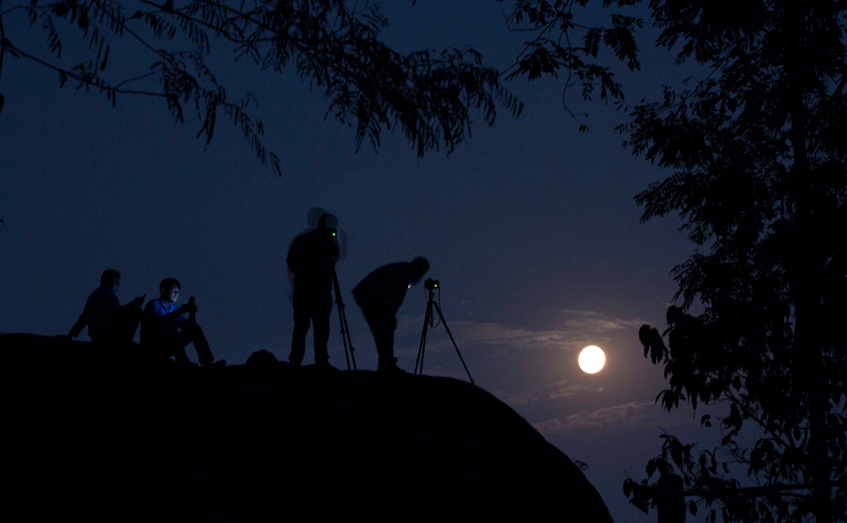 Tourists take photographs of the rising moon in Gauhati, India, Monday, Nov. 14, 2016. The brightest moon in almost 69 years lights up the sky this week in a treat for star watchers around the globe. The phenomenon known as the supermoon will reach its most luminescent in North America before dawn on Monday. (AP Photo/ Anupam Nath)